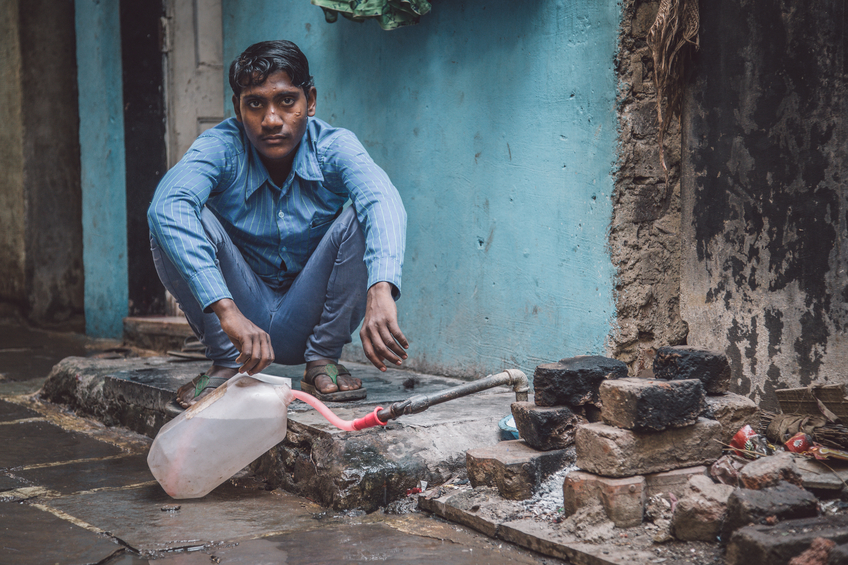 Mumbai, India - January 12, 2015: Young Indian man fills water tank in street. Dharavi slum mostly has drinkable water. Post-processed with grain, texture and colour effect.