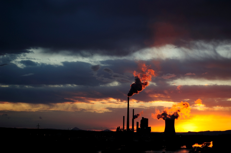 Coal power station with smoking chimneys in sunset with cloudy sky, industrial landscape