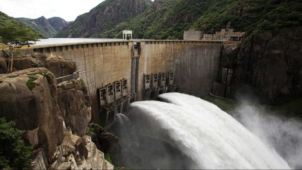 Dam spans deep river valley, with water gushing out and green-sided hills to either side